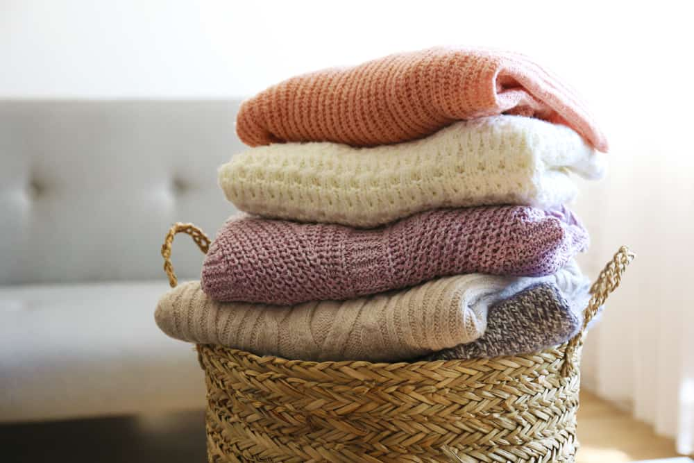 This is a look at folded and stacked sweaters in a basket.