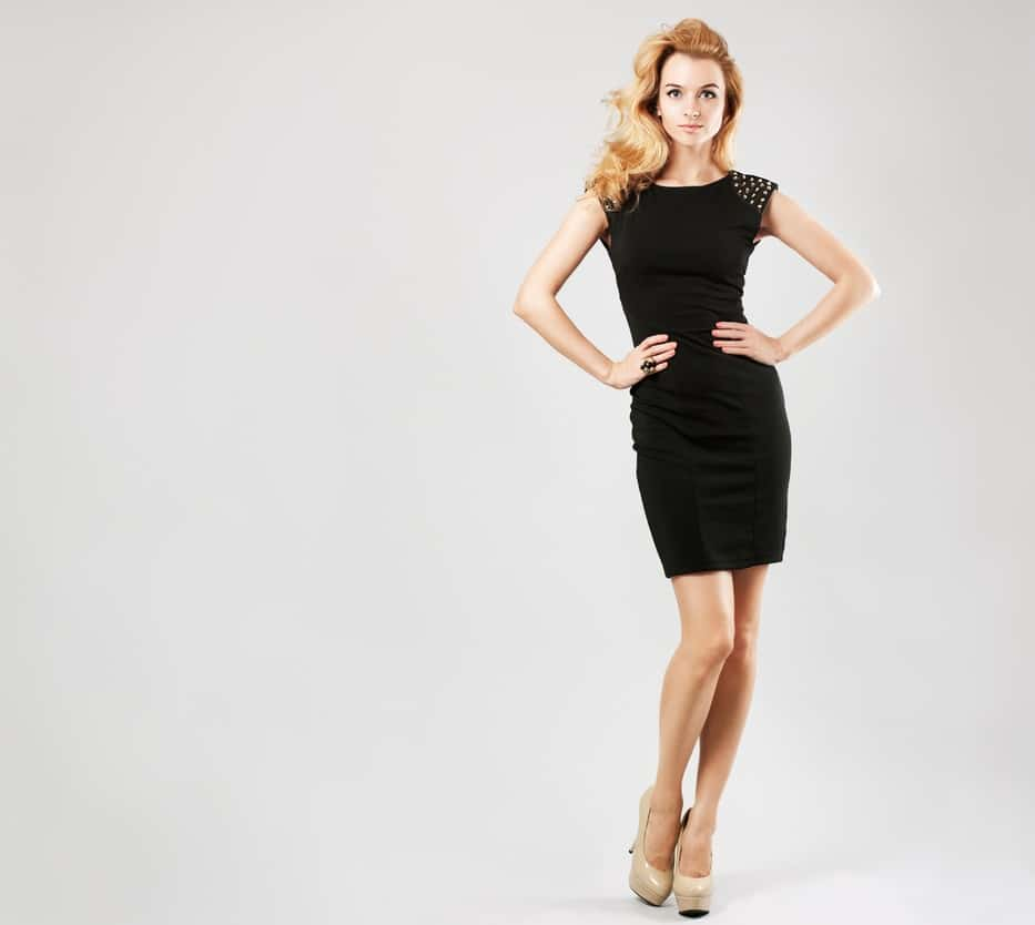 A woman wearing a little black dress and a pair of beige heels.