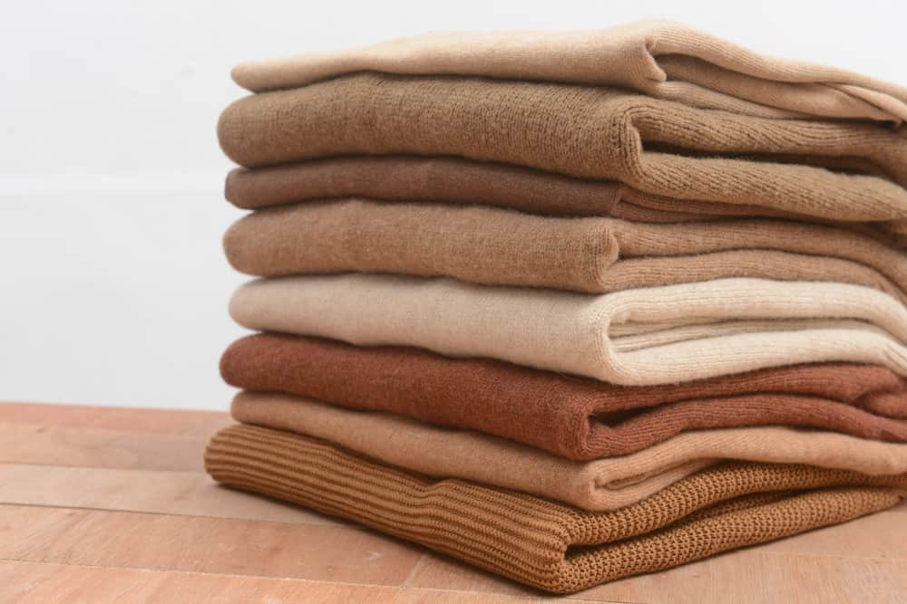 A look at a stack of folded knitted sweaters.