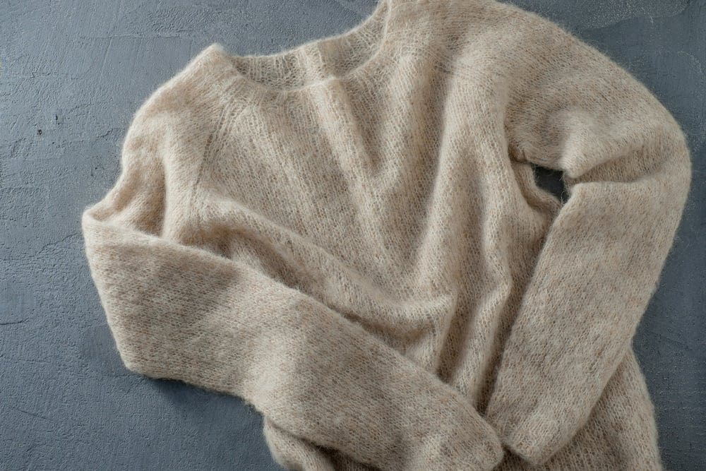 This is a close look at a pastel beige wool sweater on a concrete floor.