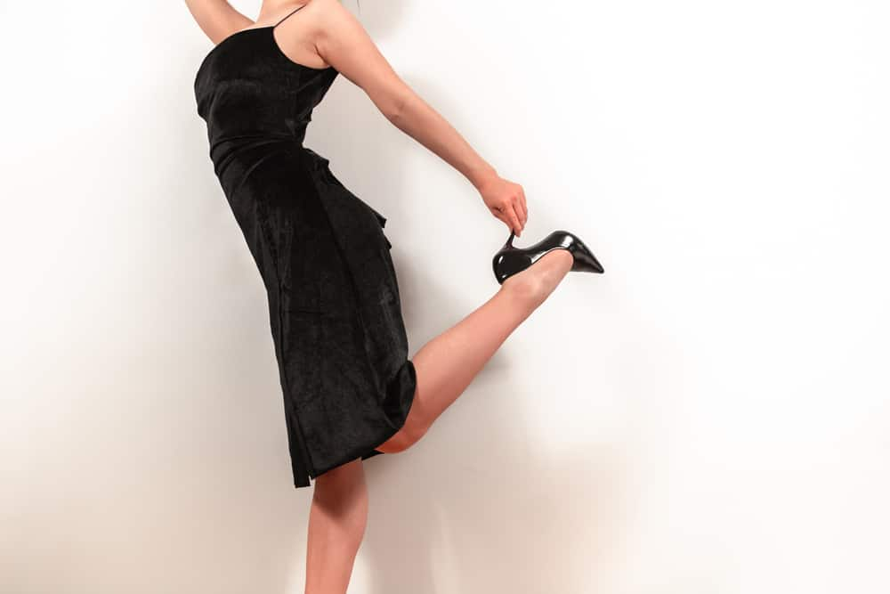 A close look at a woman wearing a little black dress and black heels.