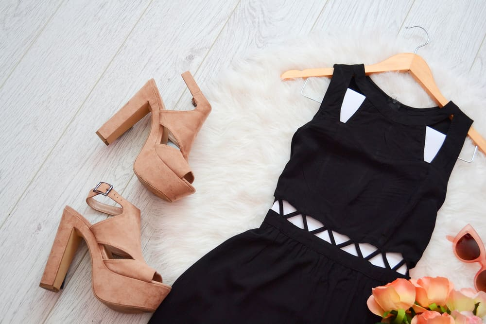 This is a little black dress with a pair of beige heels and sunglasses.