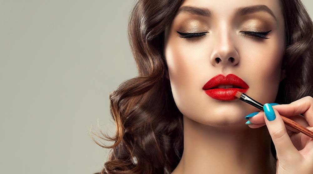 Makeup artist applying red lipstick on female model.