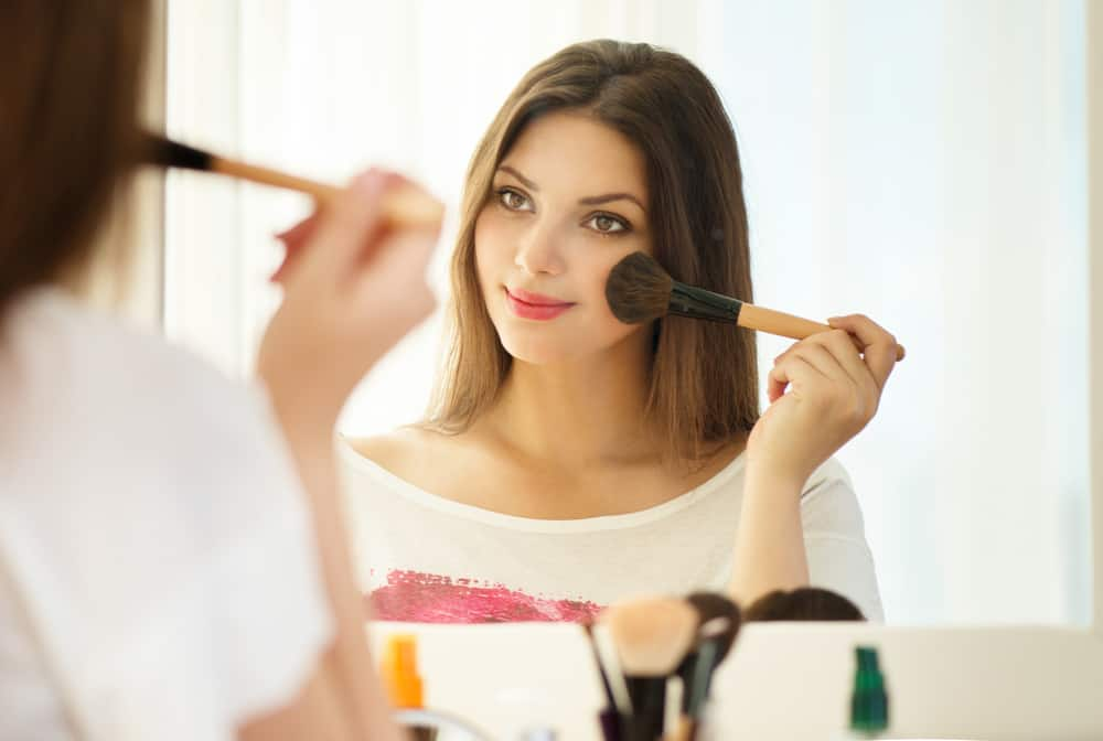 Woman applying makeup against a mirror.