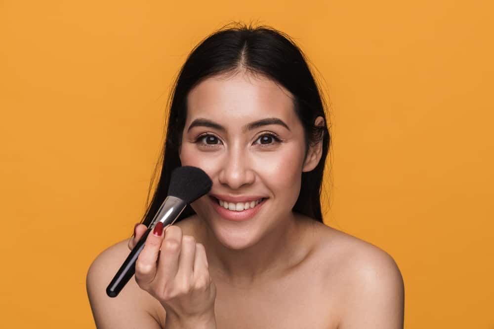 Woman applying primer with makeup brush.