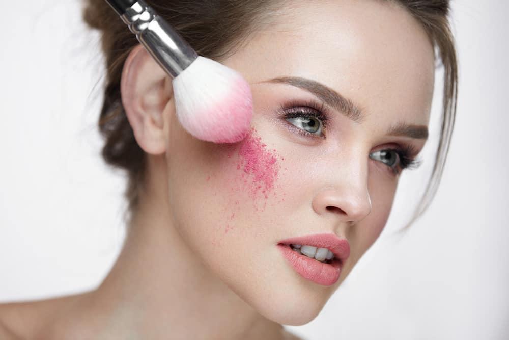 Woman applying loose blush using makeup brush.