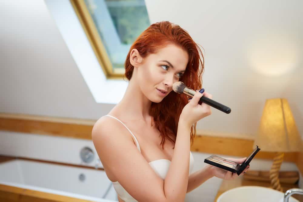 Woman applying bronzer.