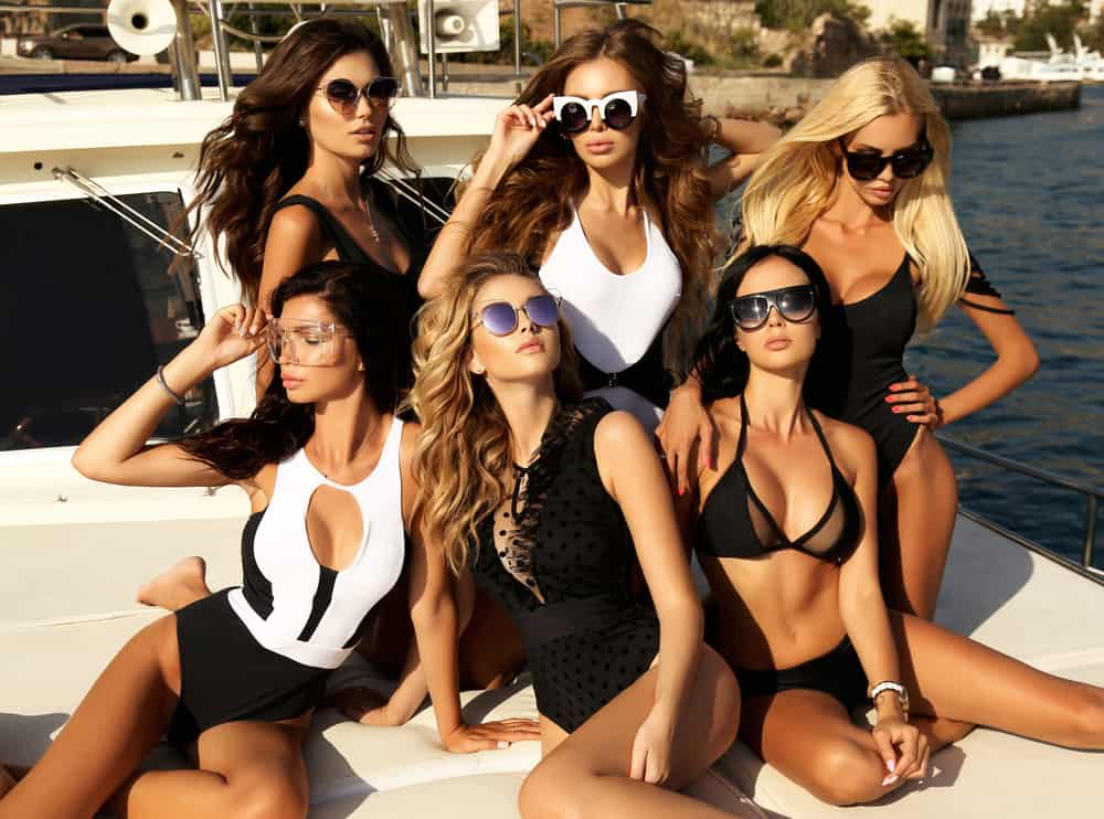 Photoshoot of female models in black and white swimsuit on a yacht.