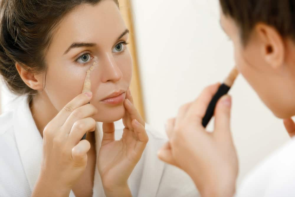 Woman using concealer for under eye circles.
