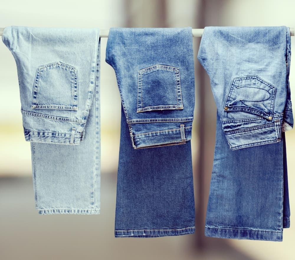 Three denim jeans hanging on a white rod.