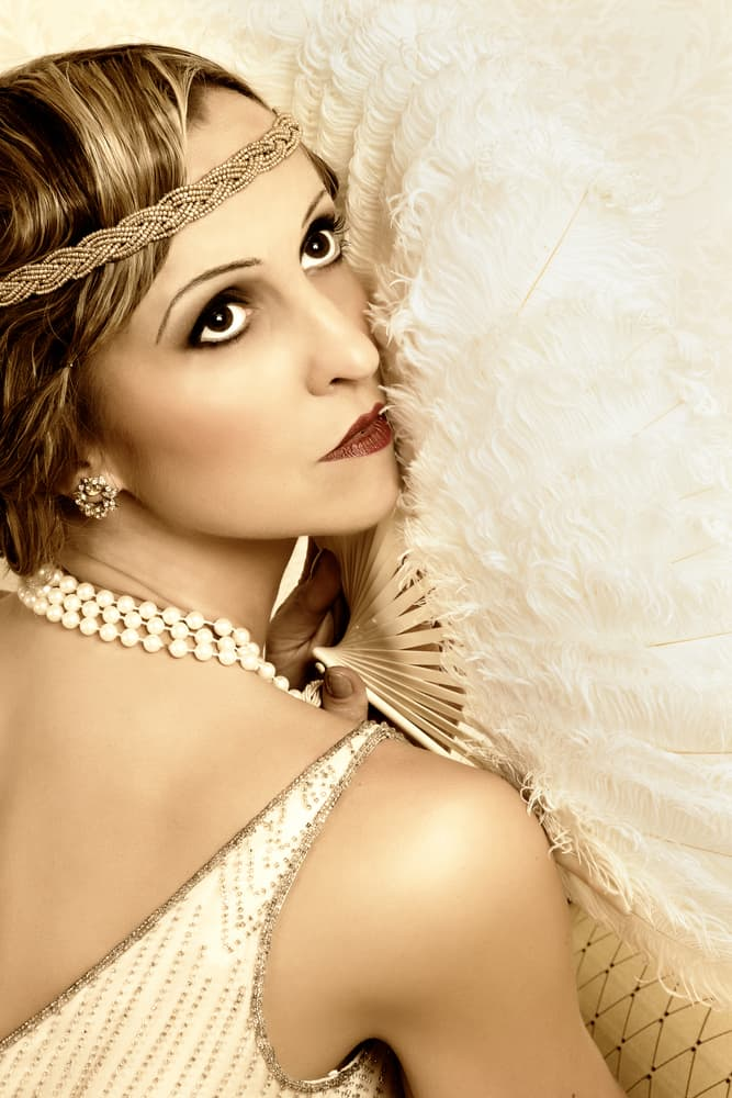 Woman with flapper dress headband holding a large, vintage fan.