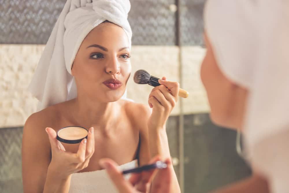 Woman in bath towel applying powder using a makeup brush.