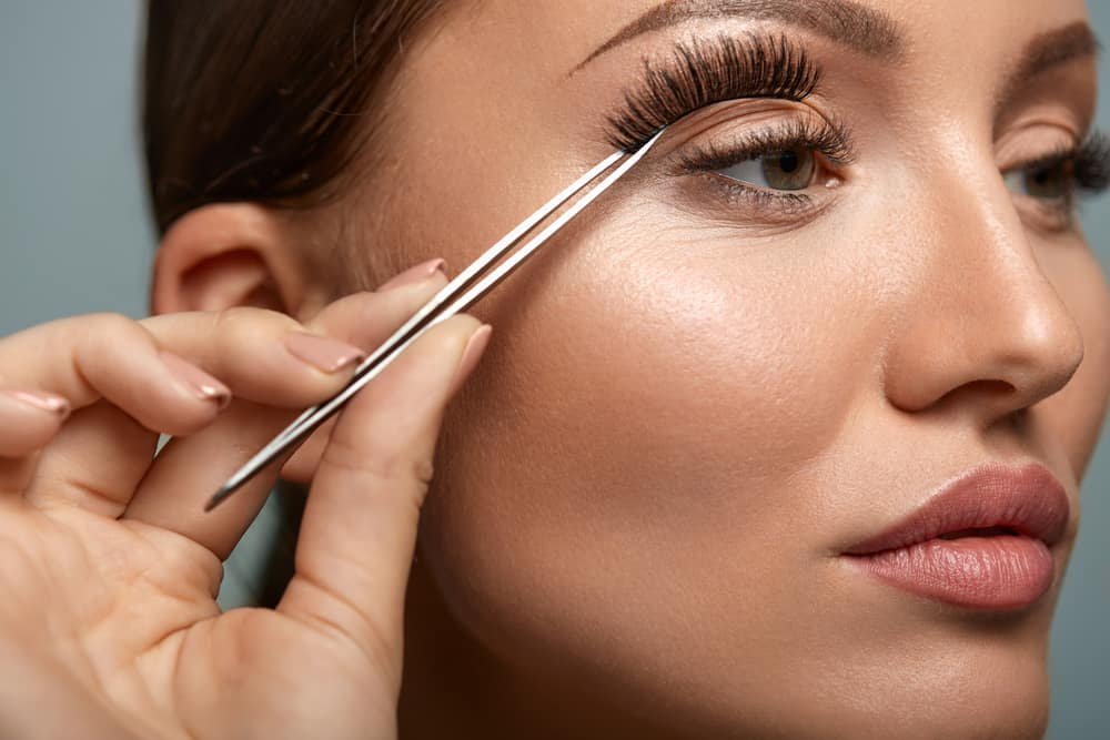 Woman applying false eyelashes with tweezers.