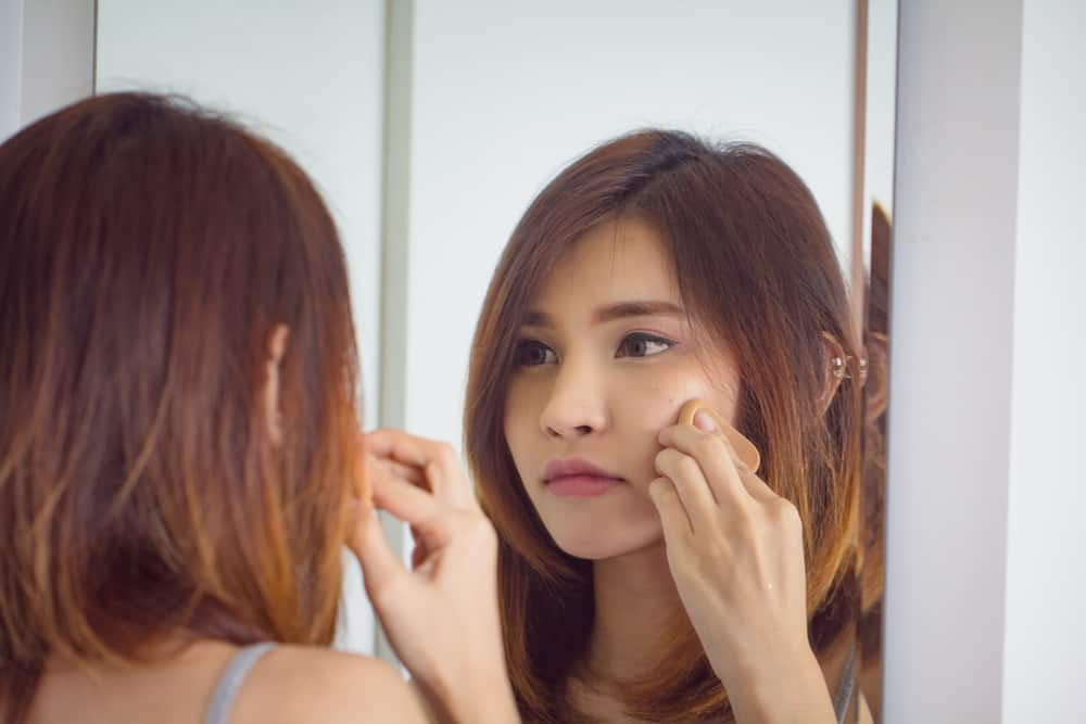 Woman applying powder puff foundation while looking at a mirror.