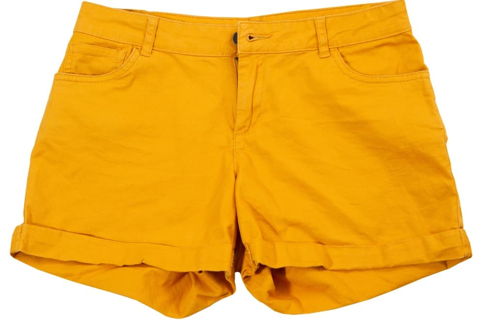 This is a close look at a pair of mustard yellow shorts with cuffs.