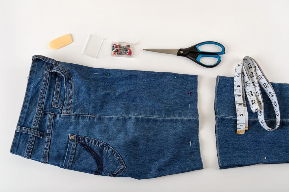 This is a close look at a pair of denim pants in the process of being converted into a pair of shorts.