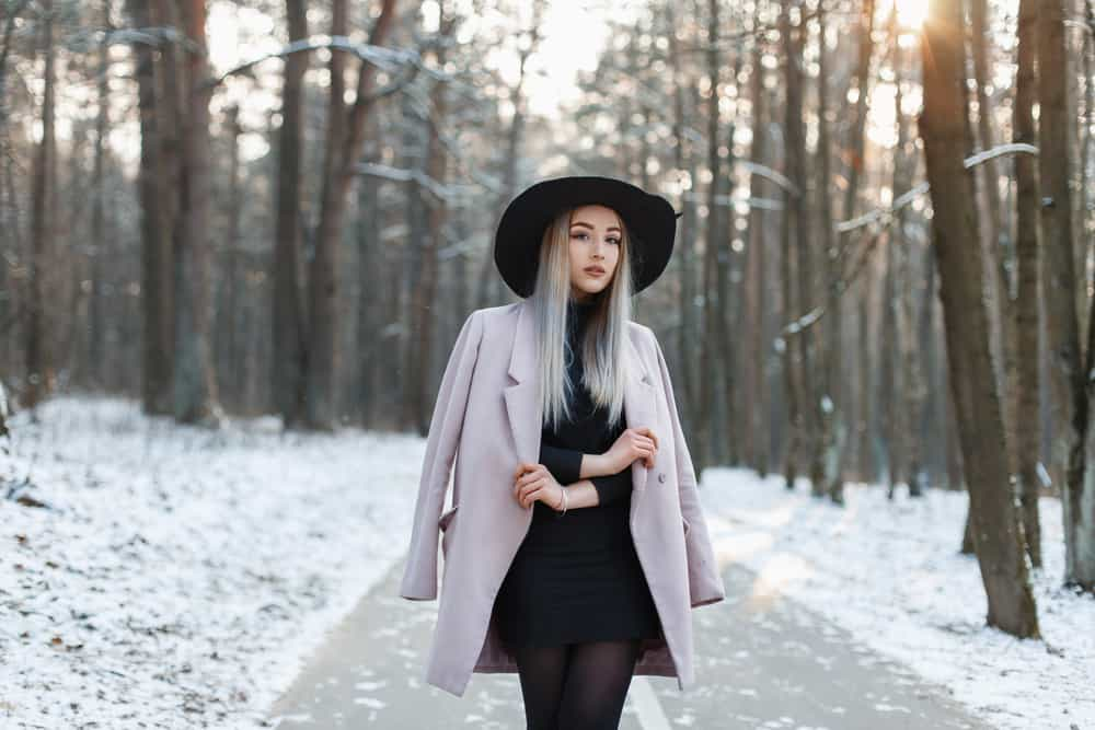 This is a woman wearing a little black dress while walking through a wintry forest.