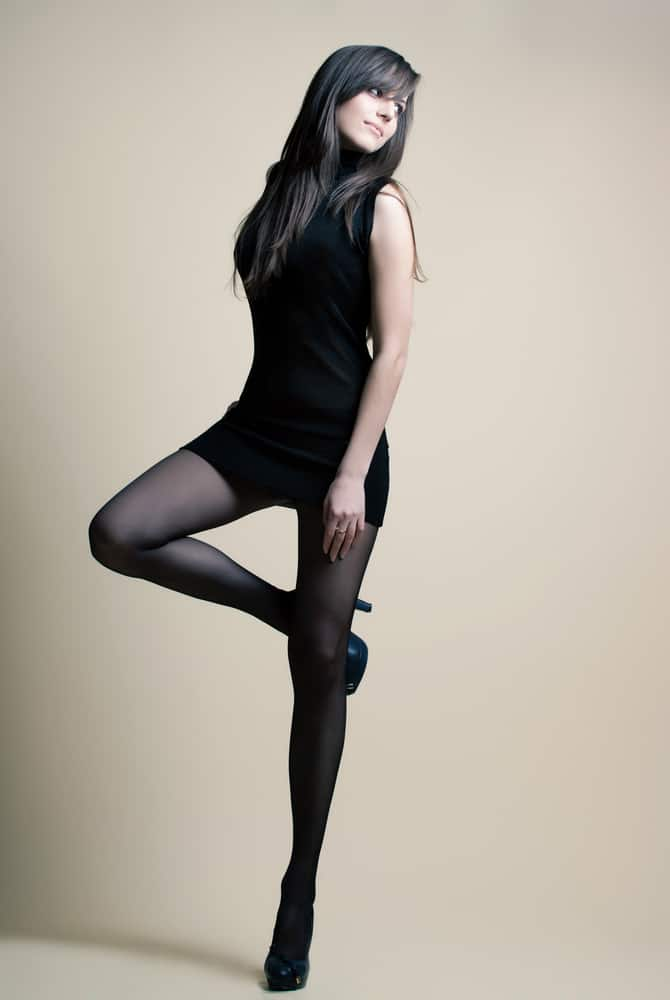 This is a woman wearing a little black dress with black leggings.
