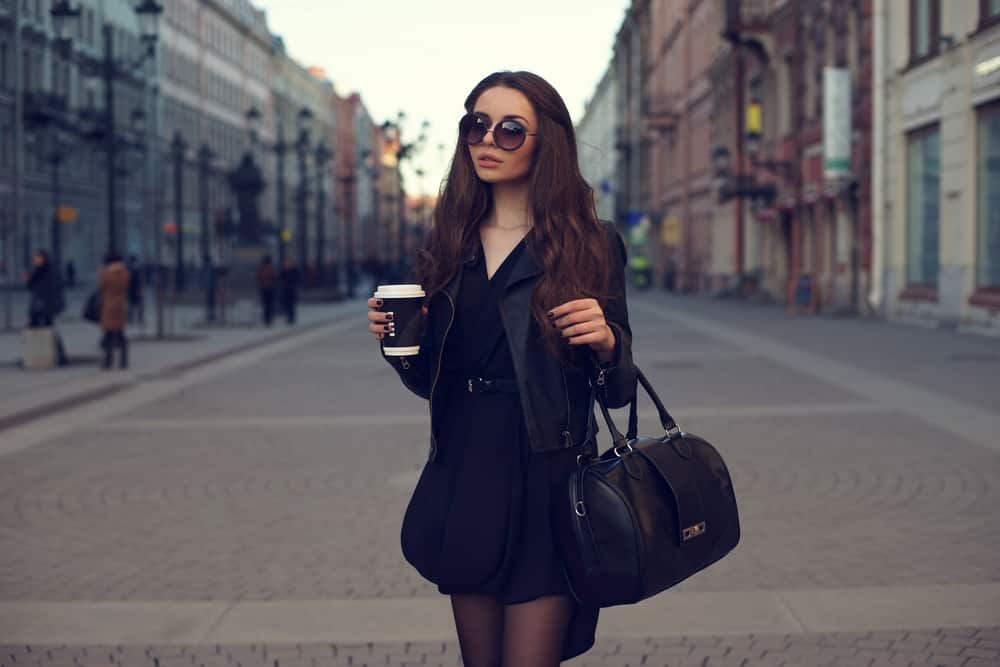 This is a woman wearing a little black dress with her black jacket and bag.