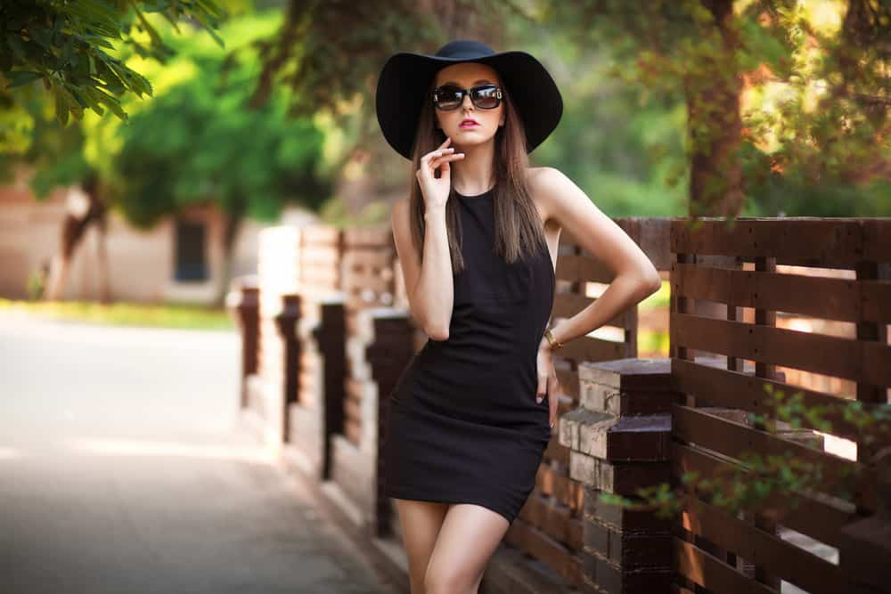 A woman wearing a little black dress at the park.