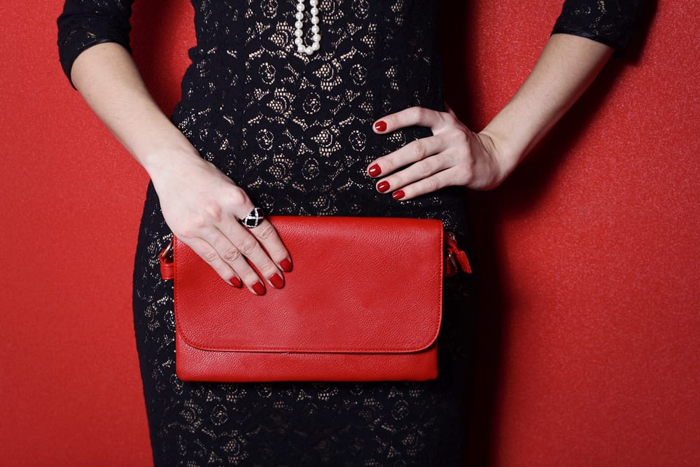 This is a close look at a woman wearing a little black dress that she paired with red accessories.