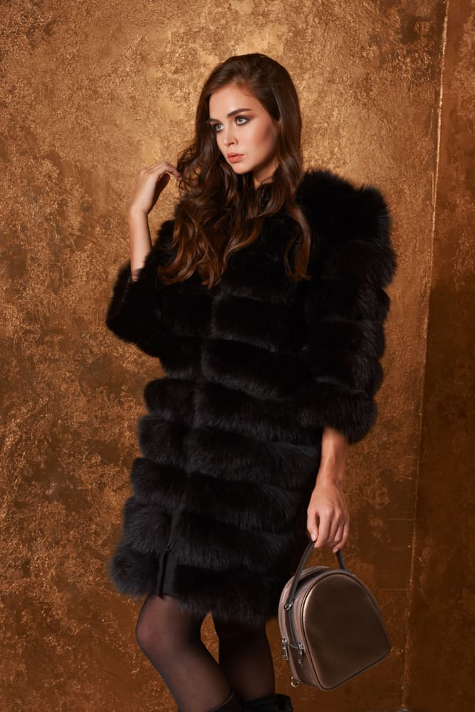 This is a woman wearing a long black fur coat.