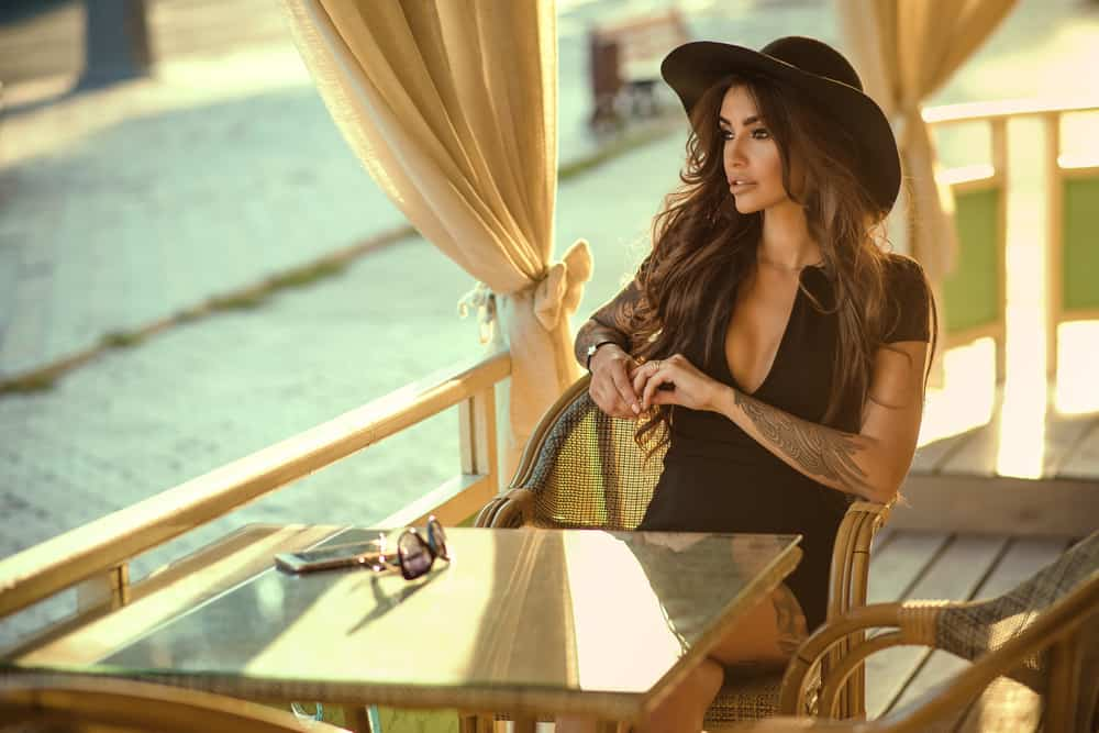 A woman sitting at a cafe wearing a black dress with a hat.