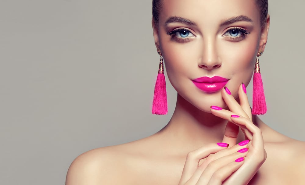 Model with pink lipstick, matching manicure, and tassel earrings.