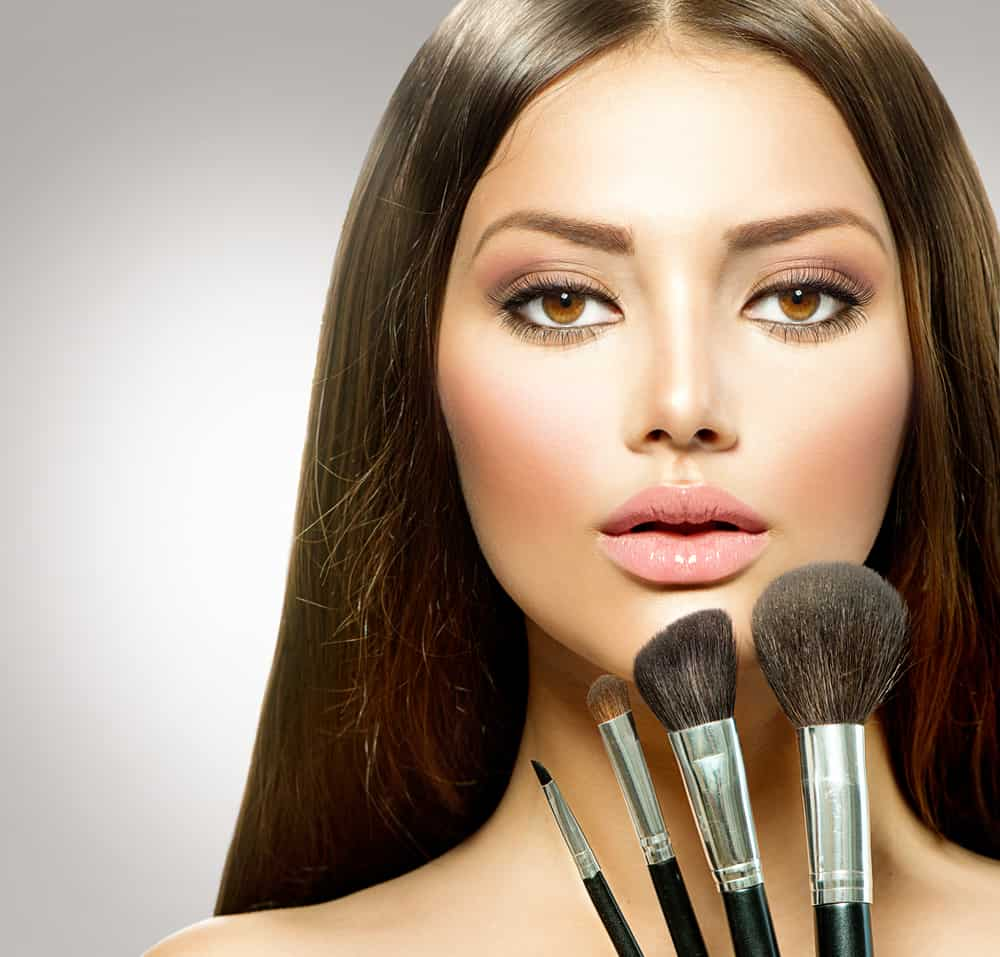Woman with natural makeup and brushes.