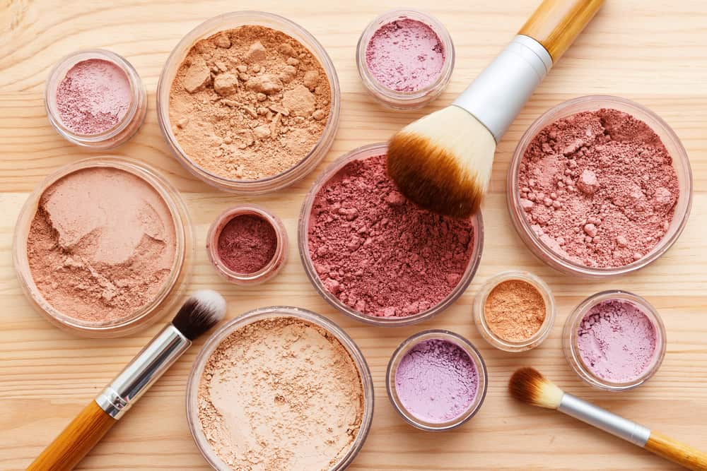 Mineral makeup cosmetics and brushes on a wooden table.