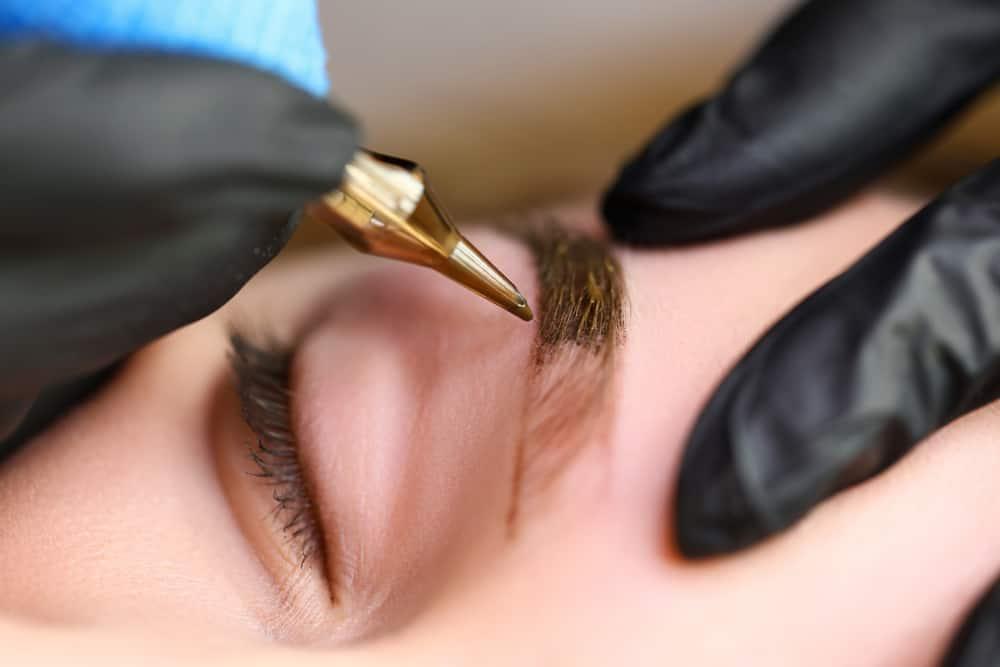 Cosmetologist performing eyebrow microblading.