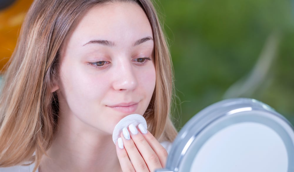 Woman removing makeup using a cotton pad in front of a mirror.