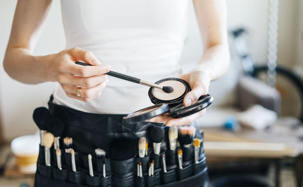Professional make-up artist with a belt bag with various brushes.