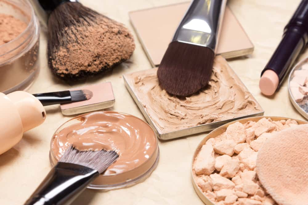 Set of makeup foundations with brushes.