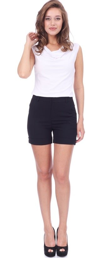 This is a close look at a woman wearing a white shirt with her black shorts.