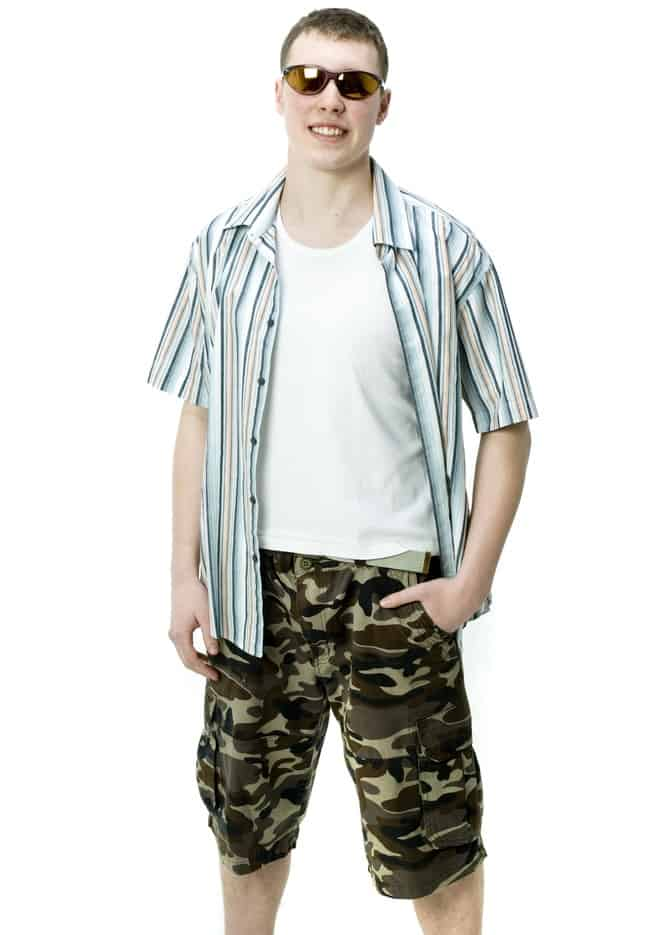 This is a man wearing a white shirt with his camo shorts.
