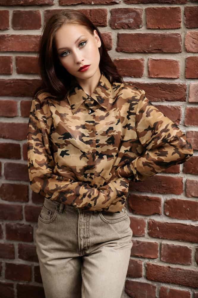 This is a close look at a woman wearing a button-down blouse with camouflage patterns.