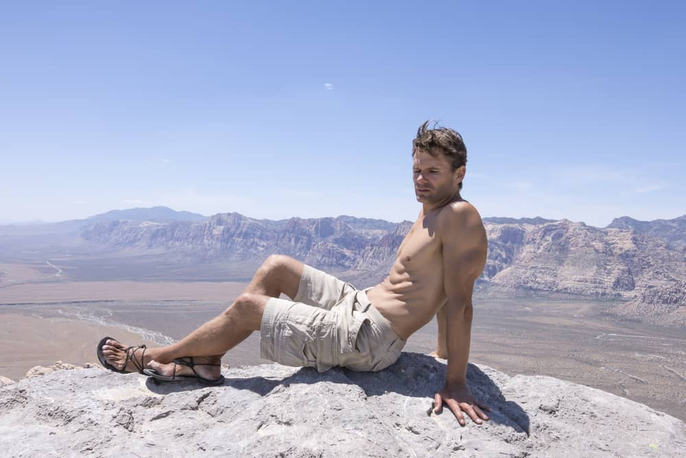 A shirtless man wearing cargo shorts and sandals on a mountain top.