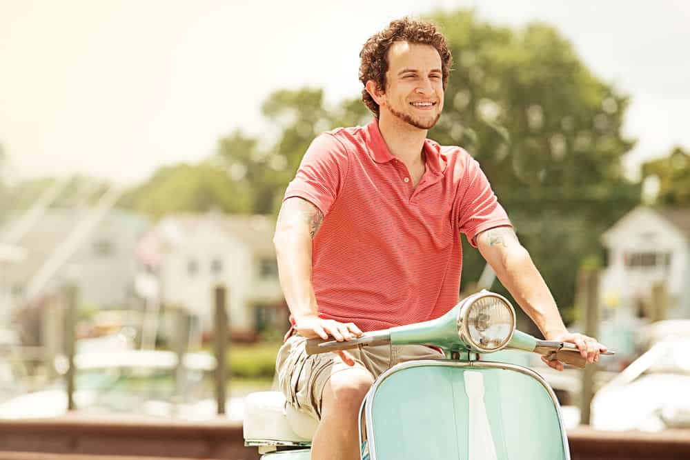 This is a man wearing a khaki cargo shorts with a salmon polo shirt while riding a scooter.