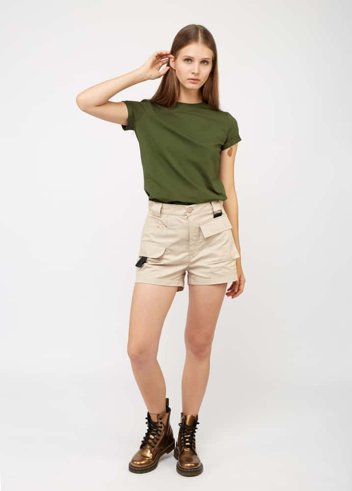 A woman wearing a pair of khaki cargo shorts with a green shirt and boots.