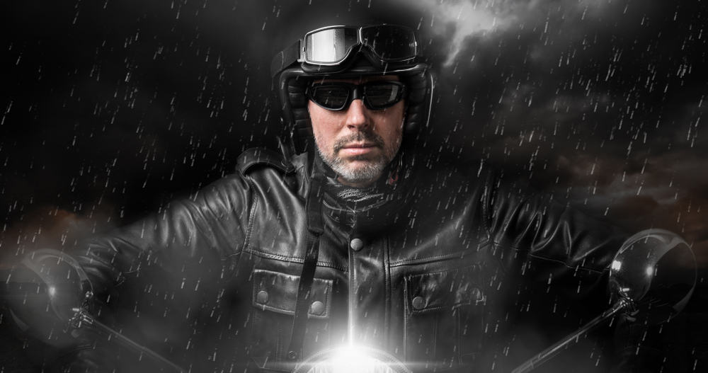 This is a close look at a biker riding in the rain.