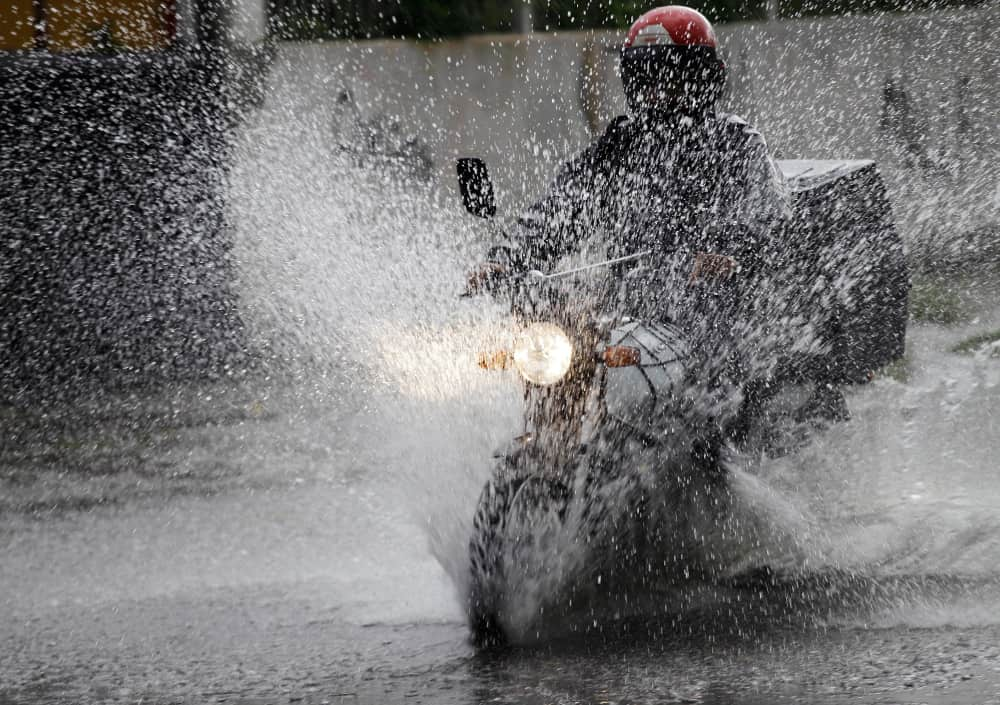 This is a motorcycle delivery worker in the rain.