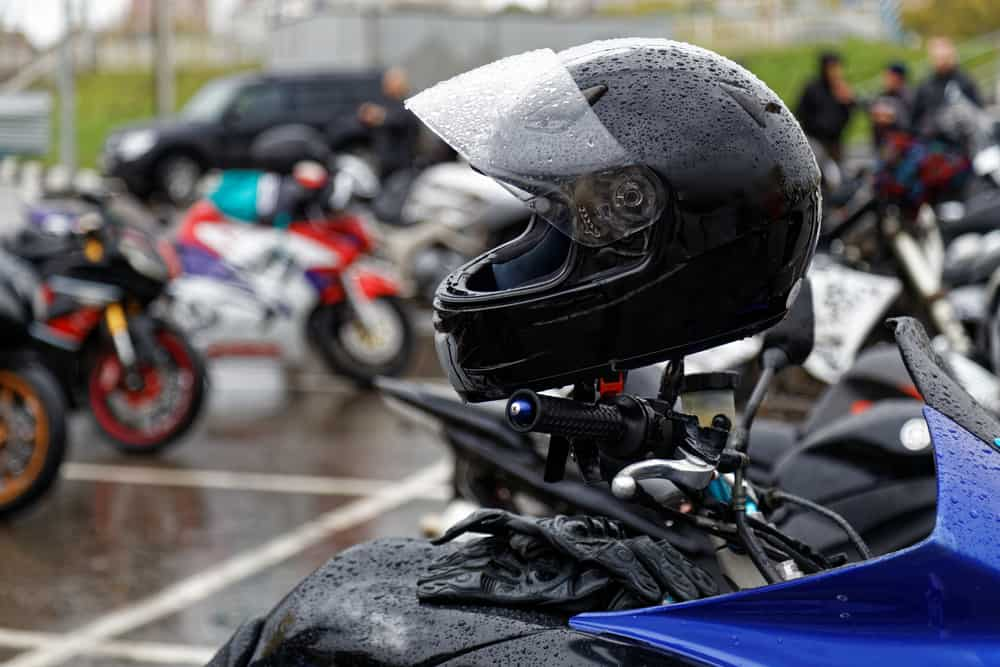 This is a close look at a wet black motorcycle helmet.
