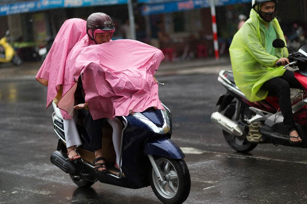 A family of three riding on a motorcycle through the rain covered with a pink tarp.