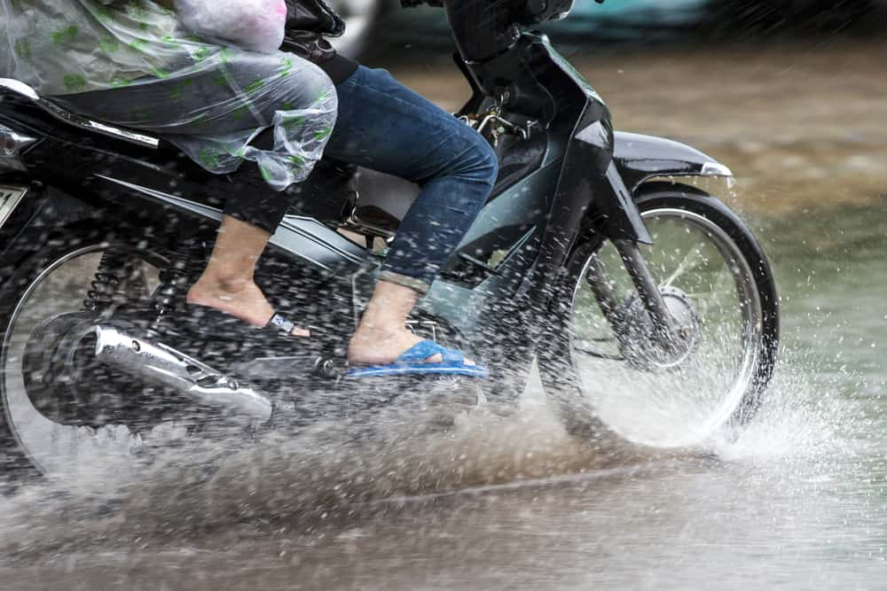 This is a couple on a motorcycle riding through the flooded street.