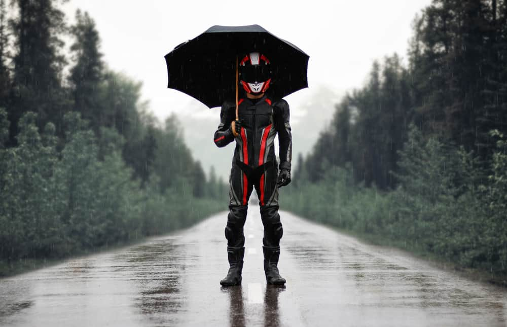 This is a rider with full gear standing under an umbrella.
