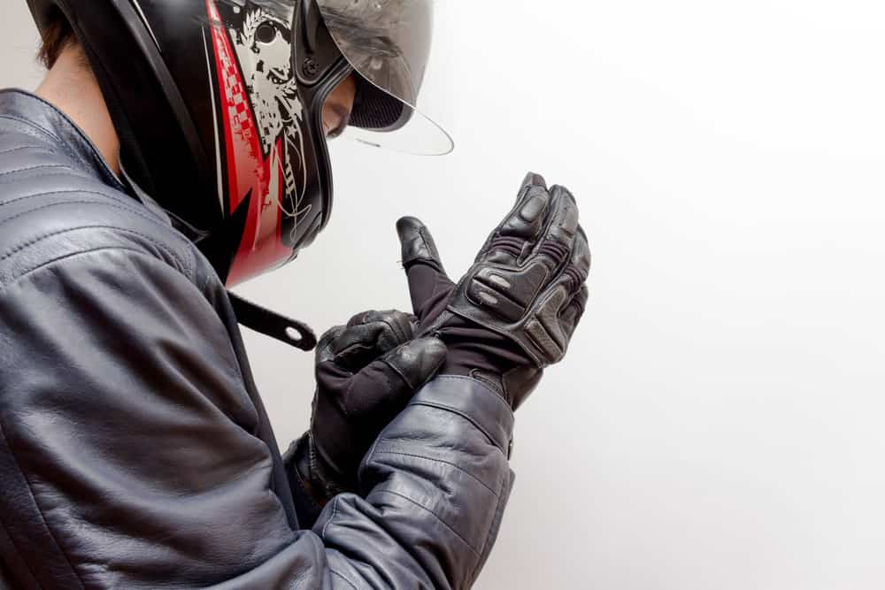 This is a rider putting on his motorcycle gloves.