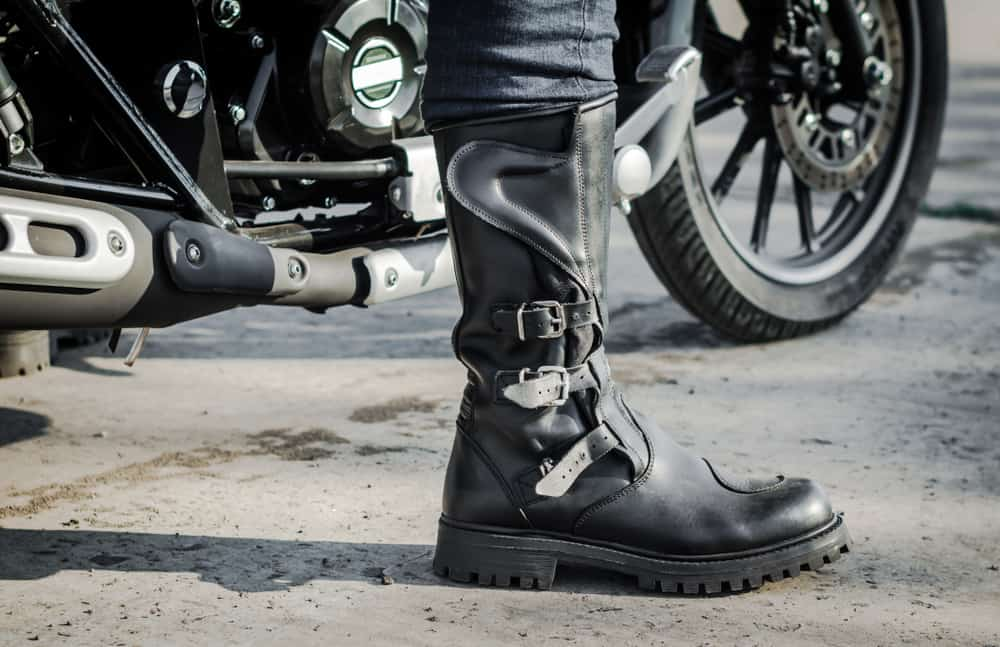 This is a close look at a rider wearing a pair of black leather riding boots.