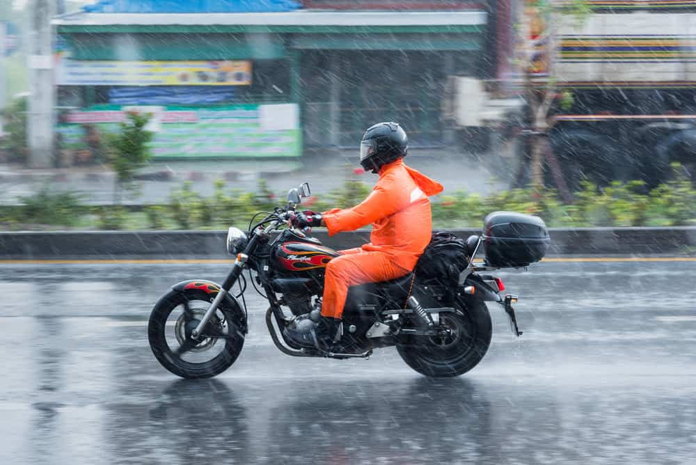 This is a rider riding his motorcycle through the rain.