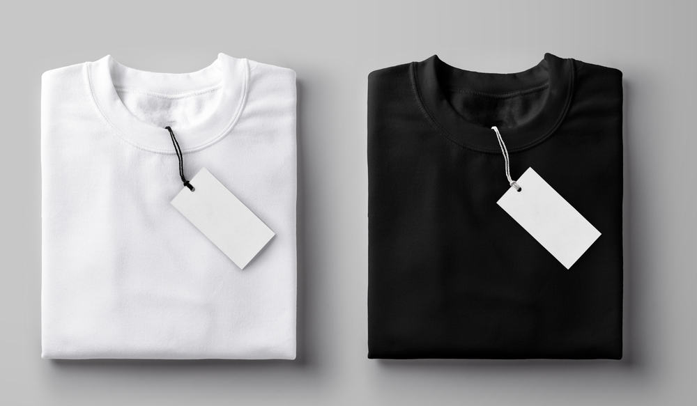 This is a close look at black and white T-shirts folded with their tags on.